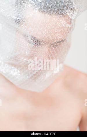 Portrait de l'anxiété les jeunes adultes de sexe masculin enveloppé dans du plastique transparent. Il est à la triste, Banque D'Images