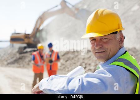 Businessman wearing hard hat in quarry