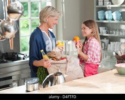 Petite-fille et femme d'épicerie de déchargement Banque D'Images