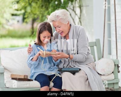 Woman giving granddaughter présents dans porch swing Banque D'Images