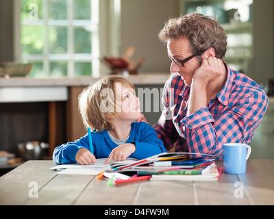 Père et fils à faire des devoirs à table de cuisine Banque D'Images