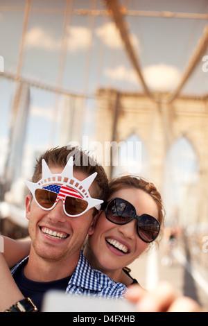 Couple dans la nouveauté des lunettes de prise de la photo sur le pont urbain Banque D'Images