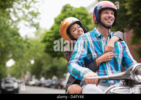 Couple riding scooter together outdoors Banque D'Images