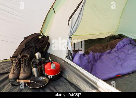 Vue intérieure d'un dôme tente montée pour le camping avec divers équipements et sac de couchage à l'intérieur de Banque D'Images
