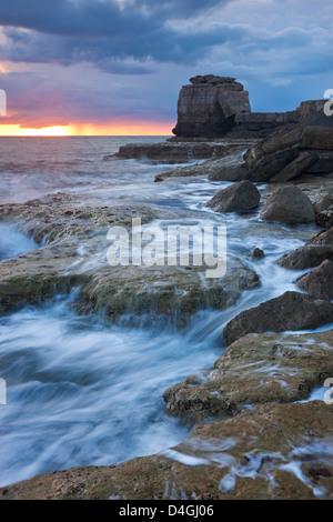 Les vagues déferlent sur la côte rocheuse de Portland Bill au coucher du soleil. Île de Portland, Dorset, Angleterre. Printemps (avril) 2012.