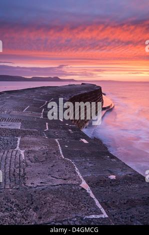 Hiver spectaculaire lever du soleil au-dessus du mur du port de Cobb, Lyme Regis, dans le Dorset, Angleterre. L'hiver Banque D'Images