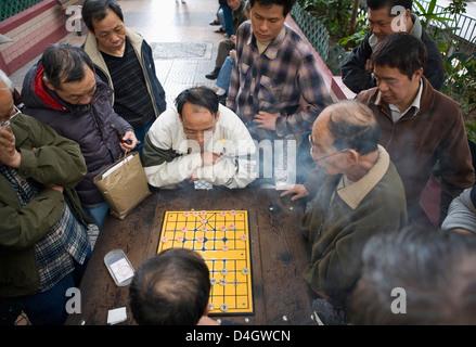 Deux hommes jouant aux Échecs Chinois chinois dans la rue, d'autres hommes regardant, Hong Kong, Chine