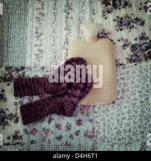 Bouteille à eau chaude avec des chaussettes tricotées main sur un lit vintage Banque D'Images