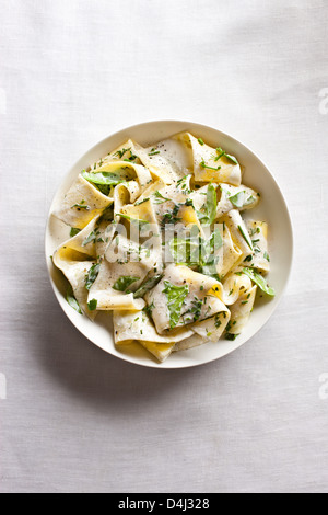 Une assiette de pâtes pappardelle avec ricotta crémeuse, bébés épinards, fines herbes et poivre noir. Banque D'Images
