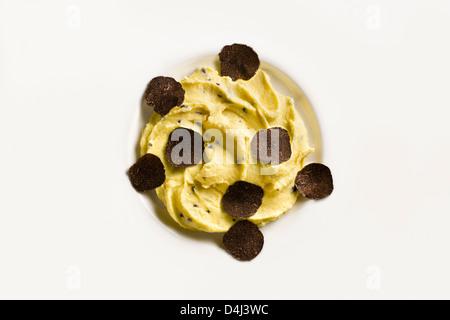 Purée de pommes de terre aux truffes noires sur une plaque blanche. Banque D'Images