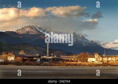 Coucher de soleil paysage scène photo d'un petit village chinois au pied d'une montagne de neige Banque D'Images