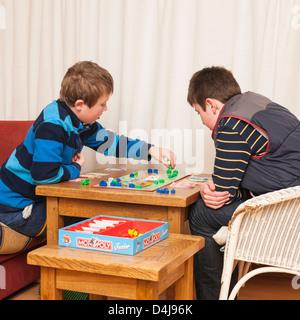 Deux garçons ( frères ) jouer jeu de monopoly junior à la maison