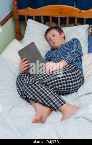 Un garçon de neuf ans à l'aide de son ipad tablet dans sa chambre à coucher Banque D'Images