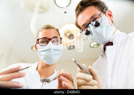 Dentiste et assistant à un traitement, dans la perspective d'un patient Banque D'Images