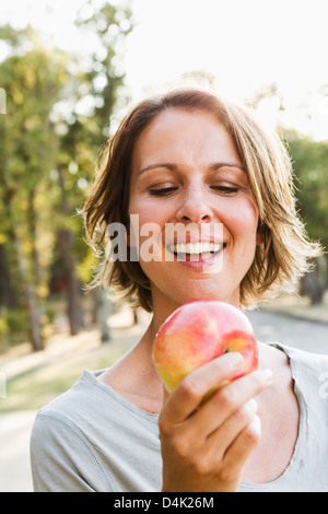 Smiling woman eating apple outdoors Banque D'Images
