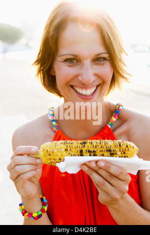 Femme de manger des épis de maïs à l'extérieur Banque D'Images