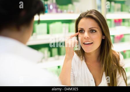 Femme parlant au greffier en magasin