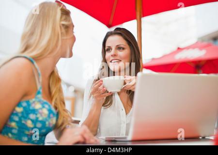 Women using laptop at sidewalk cafe Banque D'Images