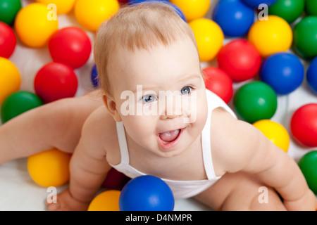 Portrait d'un adorable bébé assis parmi les boules colorées Banque D'Images
