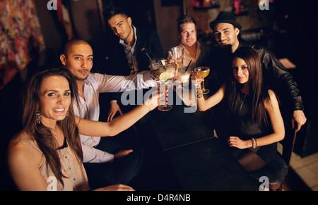 Groupe d'amis au bar élever leur verre pour porter un toast Banque D'Images