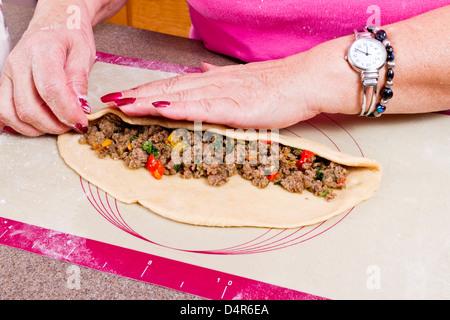 Des mains expérimentées sont des aliments traditionnels turcs d'enrubannage Pide avec du boeuf haché assaisonné. Banque D'Images