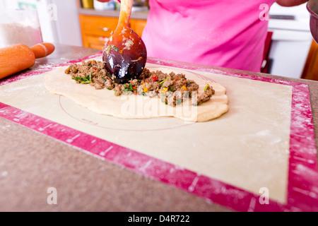 En mettant l'ustensile très utilisé sur le boeuf haché à la pâte pour rendre le Turc Pide poche. Banque D'Images