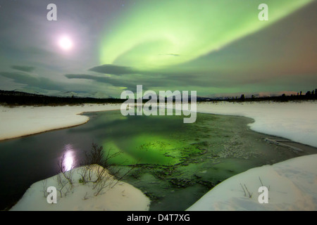 Aurore boréale et la pleine lune se couche sur une montagne et ruisseau par Fish Lake, Whitehorse, Yukon, Canada. Banque D'Images