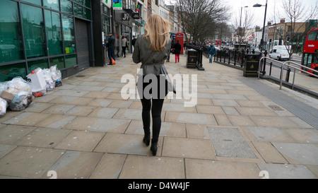 Vue arrière d'une belle jeune femme à la mode à marcher le long de la rue supérieure Islington Londres Angleterre Banque D'Images