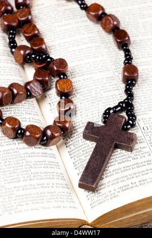 Chapelet et croix couchée sur une page de la bible.