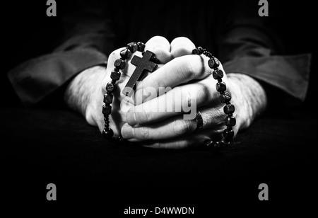 Hands holding rosary et traverser tout en priant. Banque D'Images