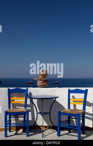 Vue sur table et chaises en face du paysage de Santorin Banque D'Images