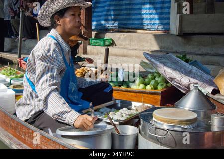 En Thaïlande, le marché flottant de Damnoen Saduak. Fournisseur local en bateau de collations le long des voies Banque D'Images