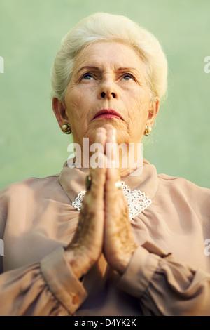 Les femmes âgées et la religion, portrait of serious woman les mains jointes priant Dieu sur fond vert Banque D'Images