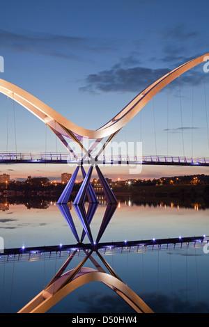 Le pont de l'infini, Stockton-on-Tees, reflétée dans le fleuve Tees au coucher du soleil.