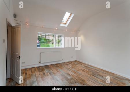 Une grande nouvelle aux hauts plafonds peints blancs inoccupés salle vide avec des puits de lumière Velux. Banque D'Images