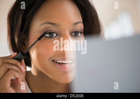 African American Woman applying makeup Banque D'Images