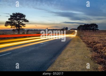 Le trafic transitant via le parc national New Forest dans le Hampshire au crépuscule Banque D'Images