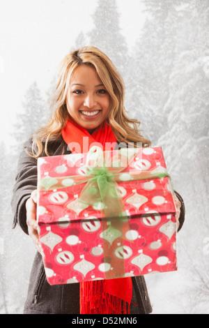 Mixed Race woman offrant des présents dans la neige Banque D'Images