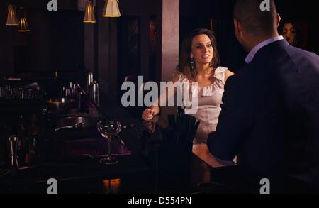 Jeune couple d'avoir une conversation au bar Banque D'Images