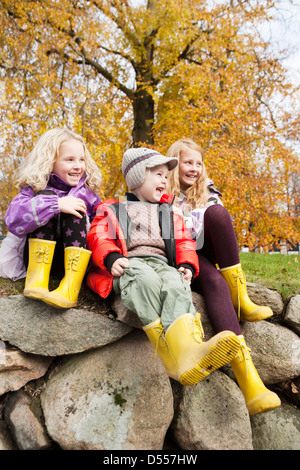 Enfants portant des bottes de pluie à l'extérieur Banque D'Images