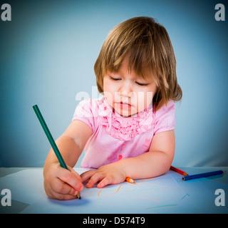 Little baby girl attire l'crayon sur un fond bleu Banque D'Images
