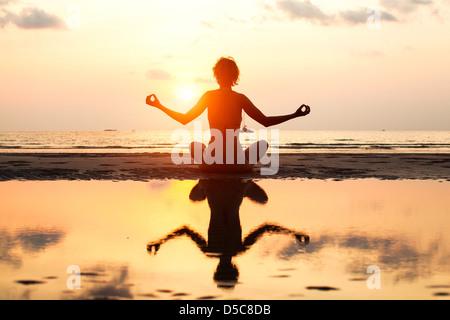 Yoga woman sitting in lotus pose sur la plage pendant le coucher du soleil, avec la réflexion dans l'eau, dans des couleurs vives.
