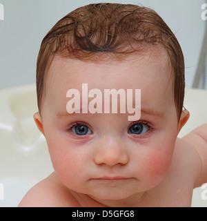 Huit mois bébé fille à bath avec de grands yeux bleus et holding lèvre inférieure avec la lèvre supérieure et de Banque D'Images