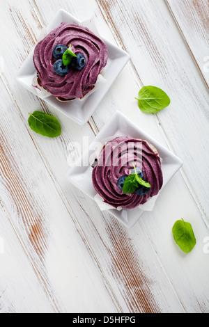 Blueberry cupcakes avec le glaçage, les bleuets et les feuilles de menthe Banque D'Images