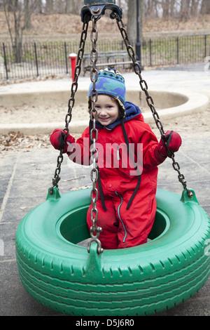Petit garçon heureux sur la balançoire pneu à la 3e Rue à Prospect Park, Brooklyn, New York. Banque D'Images