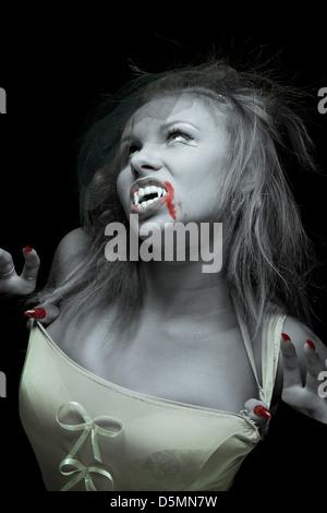 Femme-vampire avec crochets sur fond noir Banque D'Images