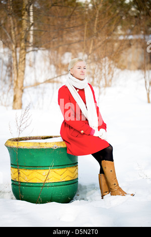 Jeune femme assise sur le grand pot de peinture vide Banque D'Images