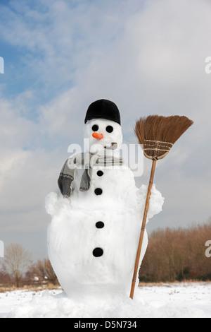 Décorées avec bonhomme heureux nez carotte, chapeau, pipe, d'écharpe et de balais dans la neige en hiver Banque D'Images