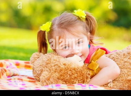 Cute smiling baby girl hugging bear soft toy, douce enfant s'amusant à l'extérieur dans la garde de jour, portant Banque D'Images