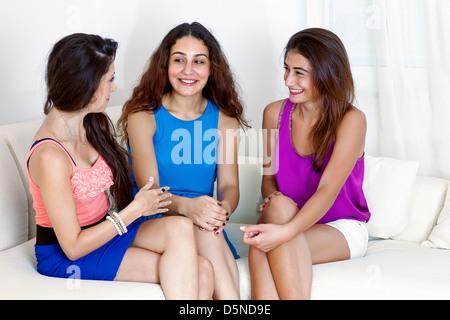 Trois amies de rire. Assis sur le canapé blanc, parler et avoir du plaisir. Fond blanc, copie-espace. Banque D'Images